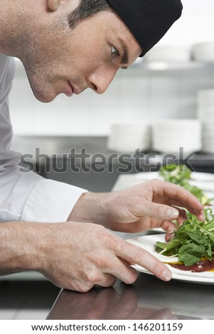 Closeup side view of a male chef preparing salad in kitchen - stock photo