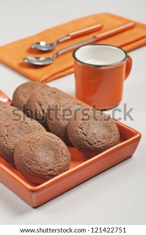 Closeup side view of biscuits in orange ceramic pan, spoons on napkin and cup of milk on white wooden background - stock photo