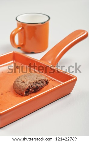 Closeup side view of broken biscuit in orange ceramic pan, cup of milk on white wooden background - stock photo