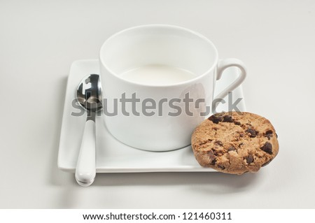 Closeup side view of cup with milk, spoon and chocolate cookie on plate on white wooden background. - stock photo