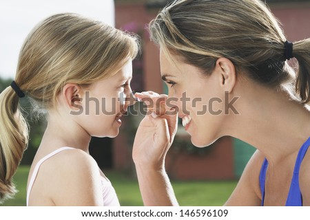 Closeup side view of mother applying sunscreen to smiling daughter's nose outdoors - stock photo
