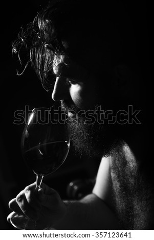 Closeup side view of one handsome sad pensive young adult man with long black lush beautiful beard and moustache holding glass with red wine indoor on blurred background, vertical picture - stock photo