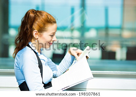 Closeup side view portrait business woman reading latest news in magazine, smiling happy, great stock market news isolated background corporate office windows. Positive human facial expression emotion - stock photo