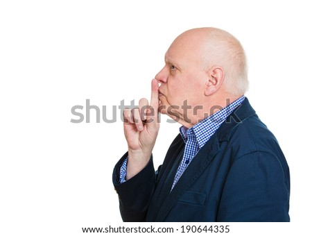 Closeup side view portrait, headshot senior, serious, man placing finger on lips with shh sign symbol, isolated white background. Negative emotions, facial expression, body language, attitude, control - stock photo