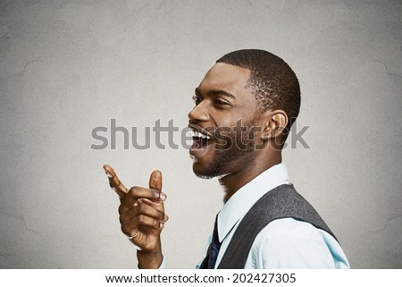 Closeup side view portrait, headshot young man, laughing, pointing with finger at someone, something, isolated black background. Positive human face expression, emotions, feelings, attitude, approach - stock photo