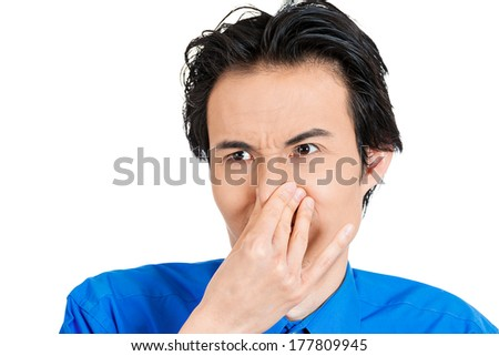 Closeup side view portrait of young man, disgust on face, pinches his nose, something stinks, very bad smell, situation, isolated on white background. Negative human emotion facial expression feeling