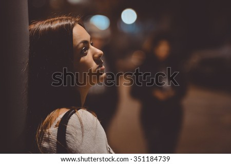 Closeup side view portrait of young sad thoughtful women leaning against street lamp at night on bokeh background copy space background - stock photo