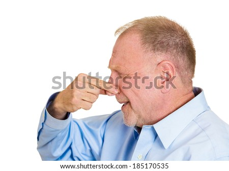 Closeup side view portrait senior mature man, disgust on face, pinching nose, something stinks, very bad smell, odor, situation, isolated white background. Negative emotion facial expression feeling