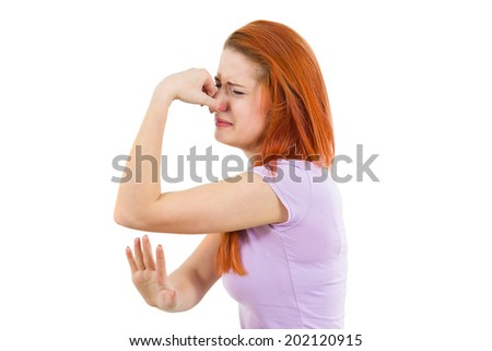 Closeup side view profile, headshot portrait young woman, disgust on face, pinches nose, something stinks, bad smell, situation, isolated white background. Negative emotions, facial expression feeling - stock photo