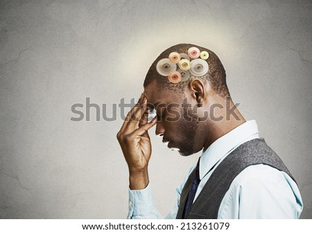 Closeup side view profile headshot thoughtful man, young guy thinking hard, gear mechanism, illustration over head isolated grey wall background. Human face expression, emotions, body language - stock photo