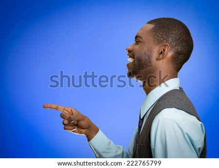 Closeup side view profile portrait happy young man laughing pointing with finger at someone something isolated blue background. Positive human face expression emotion feeling attitude approach - stock photo