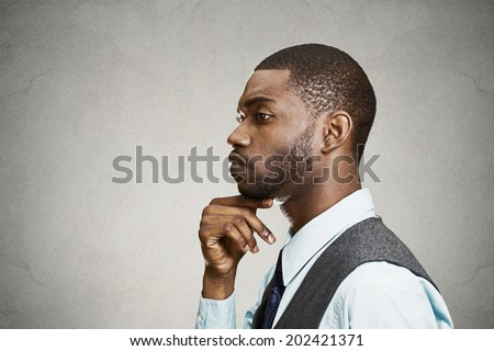 Closeup side view profile portrait, headshot young man daydreaming deeply about something with chin on hand looking down, isolated black background, space to left. Emotion facial expressions feelings - stock photo