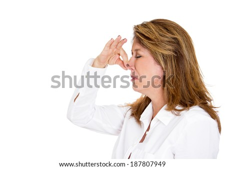 Closeup side view profile portrait, mature unhappy woman who covers her nose, looks ahead, something stinks, very bad smell, situation, isolated white background. Human facial expressions, emotions - stock photo