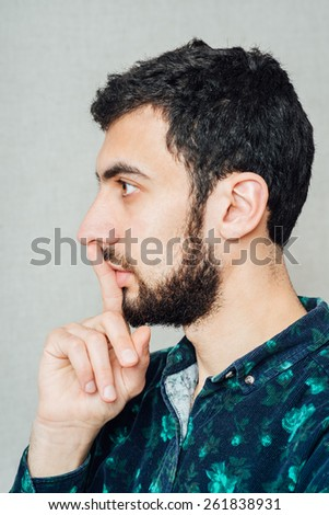 Closeup side view profile portrait of mad young man placing fingers on lips with shhh. Negative emotion facial expression feelings, body language - stock photo