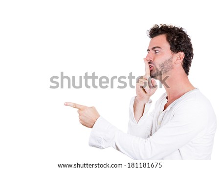 Closeup side view profile portrait of young serious man placing finger on lips, pointing to say, shhh be quiet, isolated white background. Negative facial expression emotion sign symbol, body language - stock photo