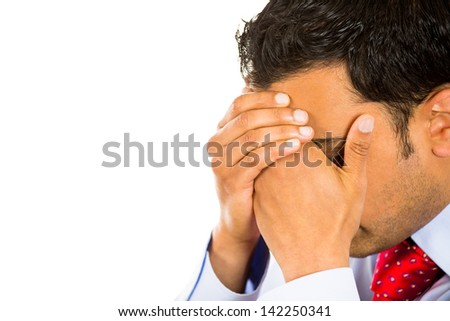 Closeup side view profile portrait, sad, bothered, stressed young man covering face with hands really depressed about something, isolated white background. Negative emotion facial expression feeling