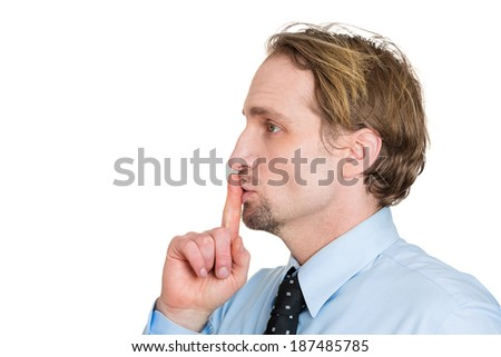 Closeup side view profile portrait, serious young man in blue shirt, black tie placing fingers on lips with shhh, isolated white background. Negative emotion facial expression feelings, body language - stock photo