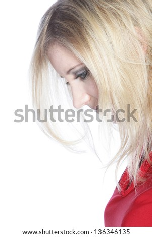 Closeup sideways portrait of the head of a dejected young woman looking down with her blonde hair partially obscuring her face - stock photo