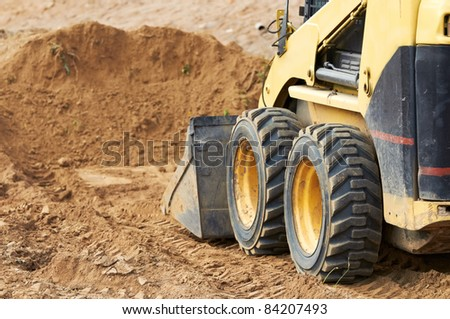 Closeup skid steer loader excavator at road construction work - stock photo