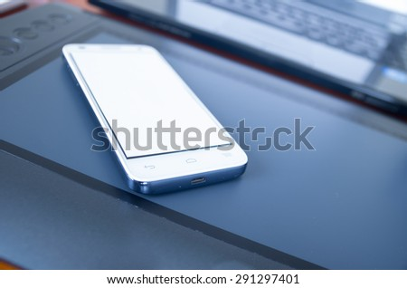 Closeup smartphone business concept with white mobile on top of digital drawboard and laptop in background from front angle. - stock photo