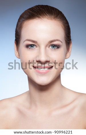 closeup smiling woman face over blue background - stock photo