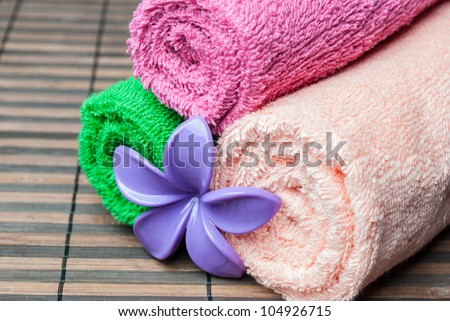 Closeup spa towels rolls and flower lying on wooden mat. Horizontal composition. - stock photo