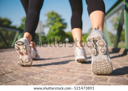 Closeup sport shoes of two young caucasian woman having their running workout at the park during a sunny day