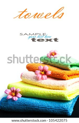 Closeup stack of colorful towels and flowers on white background. Space for your text. - stock photo