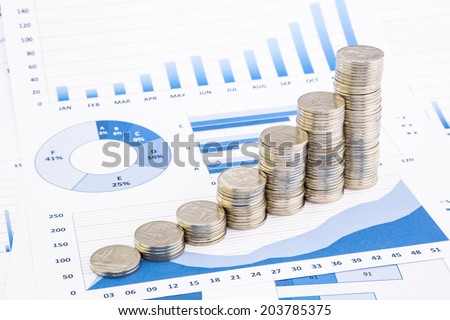 closeup stacks of  Thai baht coins on blue graphs and charts background, money and financial concepts - stock photo