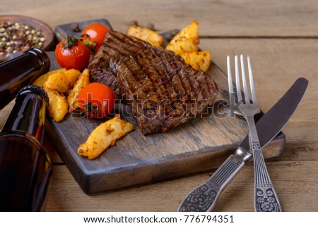Closeup steak with beer and vegetables on wooden background
