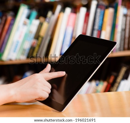 closeup student using tablet computer in library - stock photo