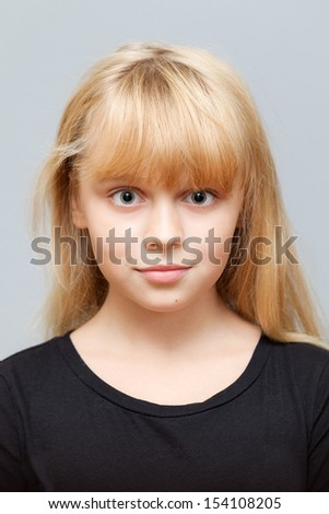 Closeup studio face portrait of little Caucasian ordinary girl isolated on gray background - stock photo