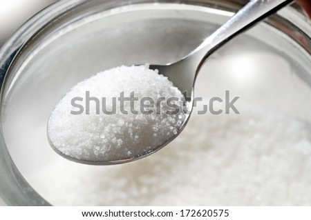 closeup studio photo of spoon full of sugar over glass jar on white background with focus on sugar crystals - stock photo
