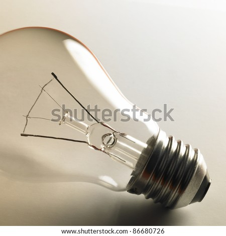 closeup studio photography of a clear electric bulb in light back - stock photo