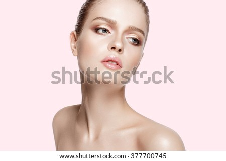 Closeup studio portrait of beautiful model with professional makeup on pink background. Soft colors. Perfect fresh skin. Blue eyes. Brunette hair.  - stock photo