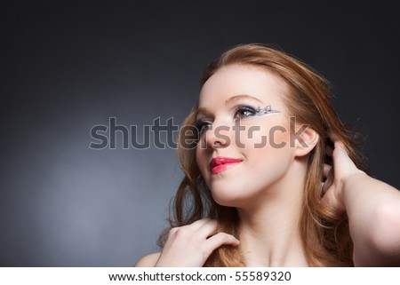 Closeup studio portrait of beautiful redheaded woman with unusual music makeup