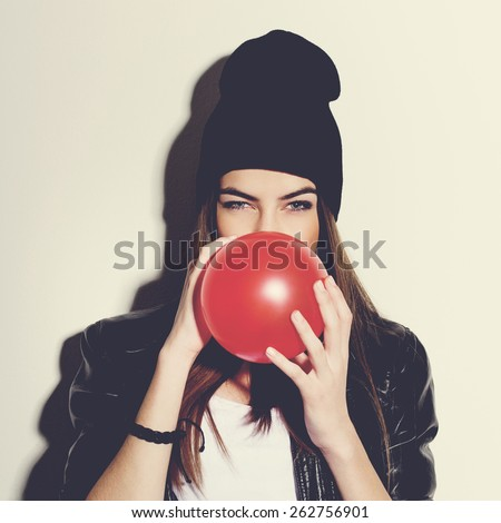 Closeup studio portrait of beautiful trendy hipster teenage girl blowing a red balloon wearing black leather jacket and black beanie hat. Square format, instagram look filter. - stock photo