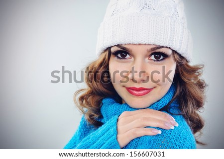 Closeup studio portrait of beautiful young girl in blue sweater and white knitted hat