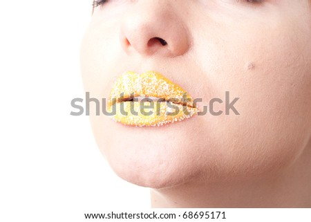 Closeup studio portrait of female lips with bright yellow lipstick sprinkled with white coconut shaving