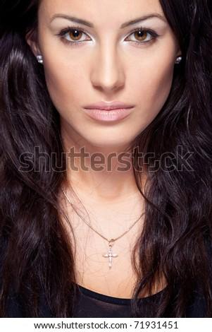 Closeup studio portrait of young attractive brunette female on dark background - stock photo