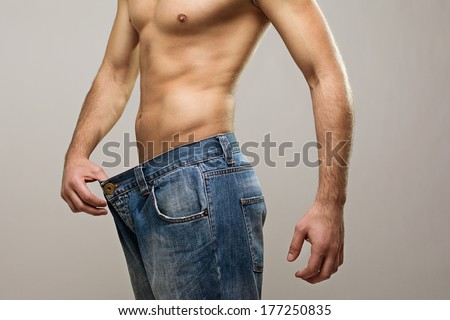 Closeup studio shot of a young Caucasian fit man wearing big jeans after diet. Copy space available. Diet, healthy lifestyle concept. - stock photo