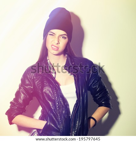 Closeup studio shot of attractive hipster teenage girl with beanie hat making arrogant facial expression showing attitude. Square image with instant filter applied. - stock photo