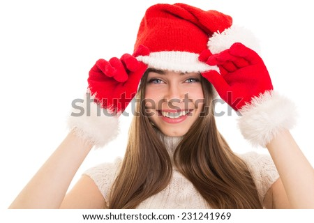 Closeup studio shot of cute Caucasian teenage girl with Christmas hat and gloves smiling looking at camera isolated on white background. Christmas and New Year concept. - stock photo