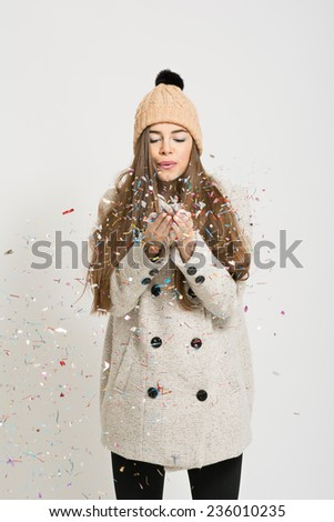 Closeup studio shot of cute young Caucasian brunette woman blowing confetti. Fashionable teenage girl in coat and beanie hat with colorful confetti. No retouch. - stock photo