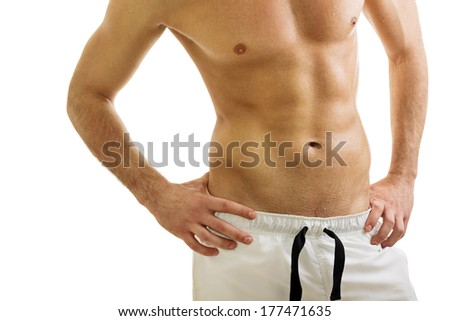 Closeup studio shot of handsome fit shirtless Caucasian young man wearing white shorts. Isolated on white background. Fitness, bodybuilding, man's body concept.