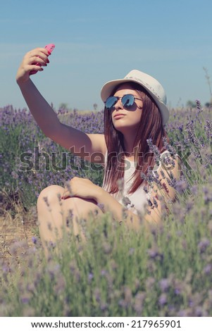 Closeup summer portrait of young happy woman makes selfie. Photo toned style instagram filters - stock photo