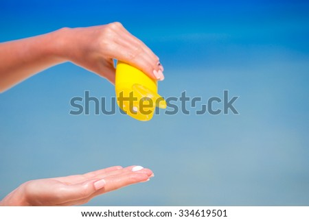 Closeup suncream bottle background blue ocean and sky - stock photo