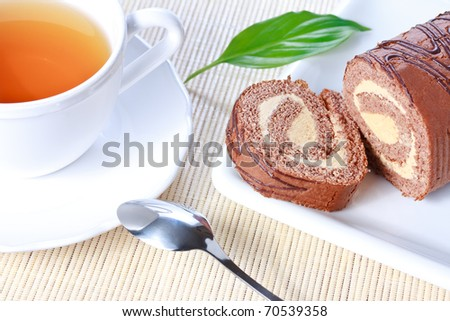 Closeup swiss roll with condensed milk cream on ? white plate and a cup of tea - stock photo