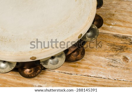Closeup take of a tambourine on a wooden table - stock photo