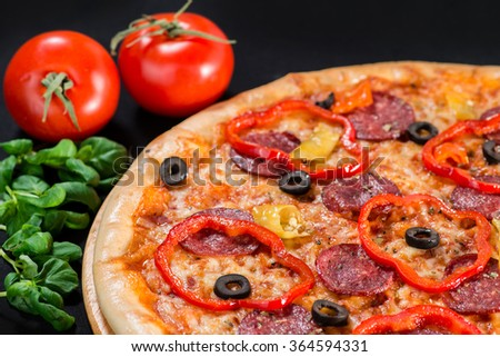 closeup Tasty pizza with tomatoes, mushroom, sausage, basil and chili pepper on a black background